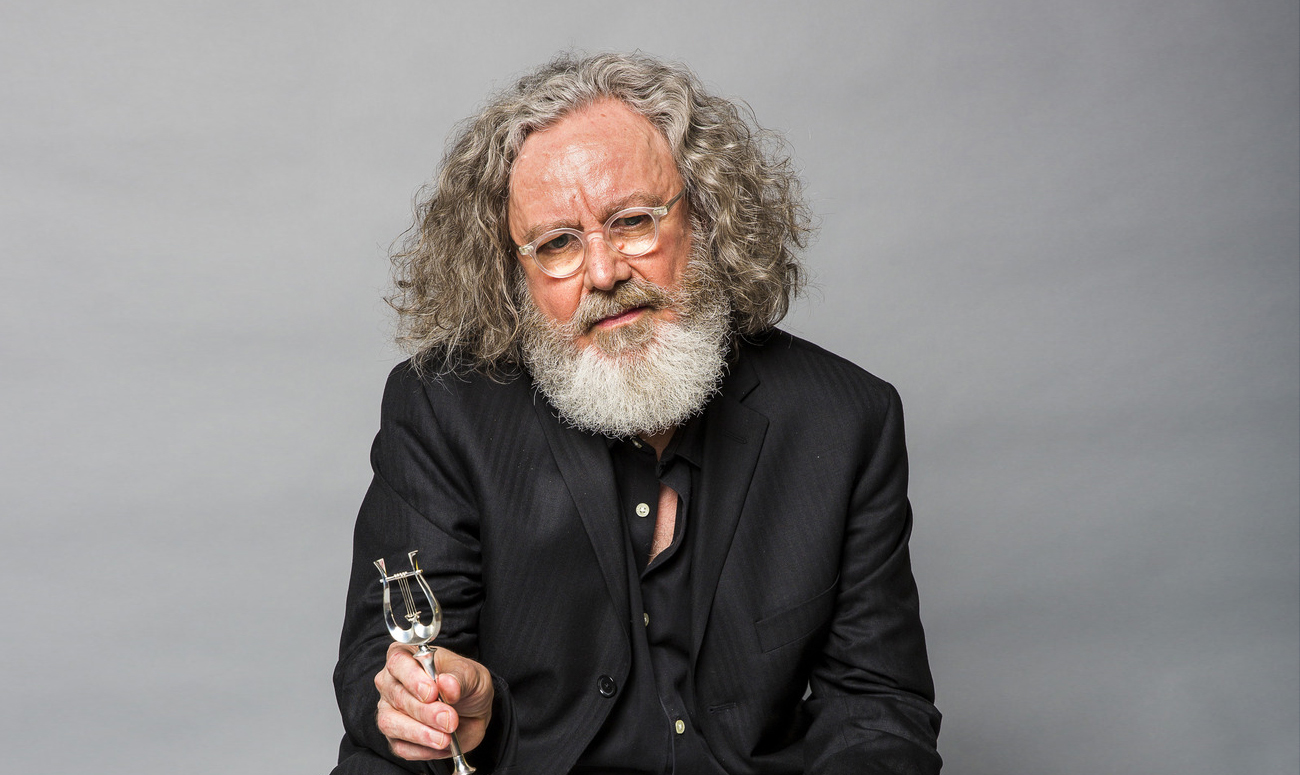 Portrait of composer James Dillon at awards ceremony on a grey background